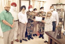 A member of NCCHWO team presenting Appreciation Certificate to Army Commandant Brig K J Singh.