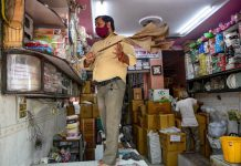 A shopkeeper cleans his shop that was reopened after unlocking process of COVID-19 lockdown began, at the Chandni Chowk market, in New Delhi.