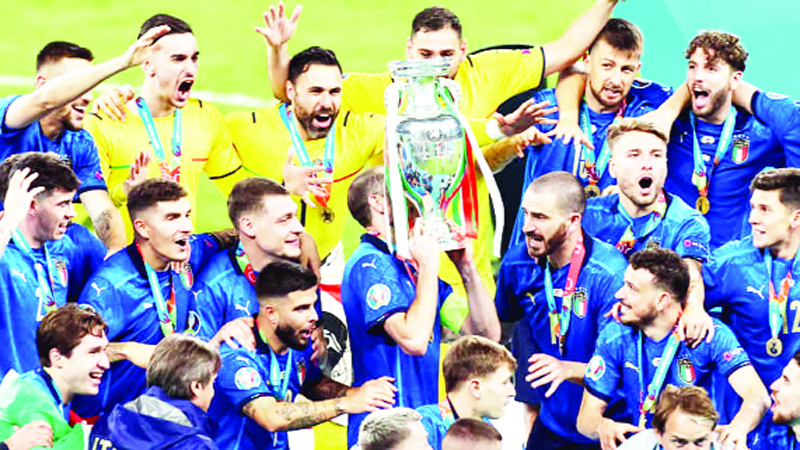 Italian soccer team celebrating victory against England by holding trophy.