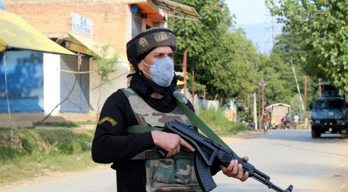 A security personnel stands alert at the site of encounter in Anantnag on Saturday. — Excelsior/Sajad Dar