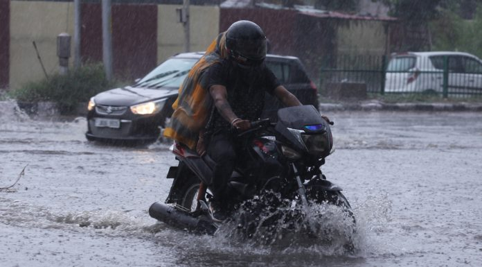 A bike rider moving through a flooded road in Gandhi Nagar area of Jammu on Saturday. — Excelsior/Rakesh