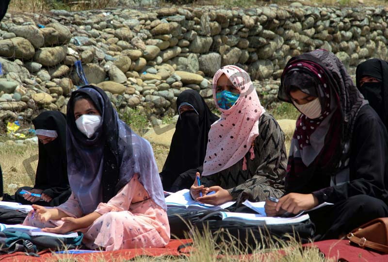 Students wearing protective face masks attend an Open-Air-Class in Tangmarg area of Baramulla district. —Excelsior/Aabid Nabi