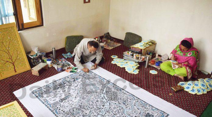 An award-winning 'Paper Mache' artist in Srinagar, Maqbool Jan making a map of Srinagar city on a cloth by using 'Paper Mache' techniques. —Excelsior/Shakeel