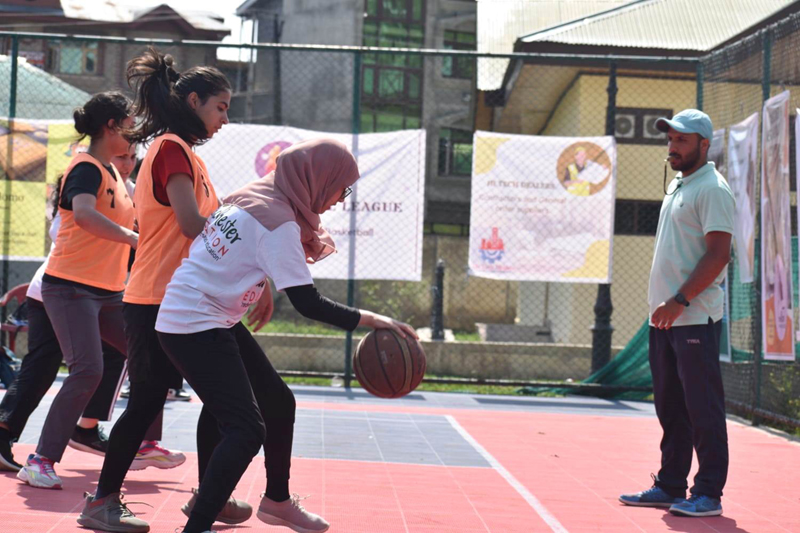 Players in action during Basketball match being played at Gindun Sports Center Srinagar on Tuesday.