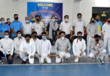Fencers posing for group photograph with dignitaries at Indoor Hall MA Stadium.