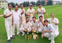 Winning team posing for a group photograph alongwith trophy at KC Sports Ground Jammu on Sunday.