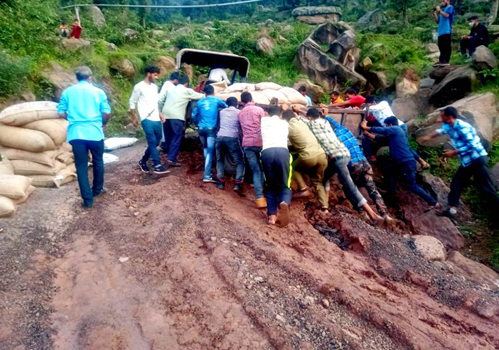 Villagers pushing up a loaded tractor trolly to make way on muddy PMGSY road. -Excelsior/K Kumar