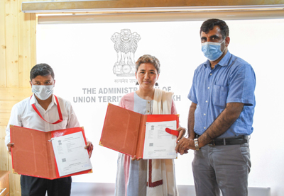 Official displaying copies of MoU signed for restablishing Helpline for senior citizens in Ladakh UT.