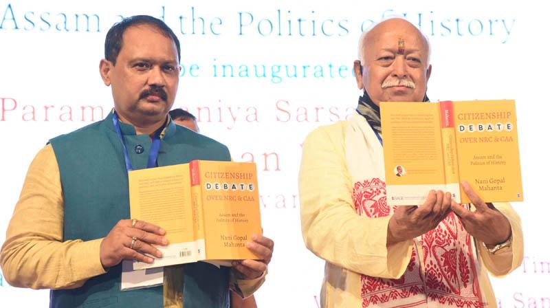 Rashtriya Swayamsevak Sangh (RSS) chief Mohan Bhagwat and author Dr Nani Gopal Mahanta launching the book 'Citizenship Debate Over NRC and CAA' in Guwahati on Wednesday. (UNI)