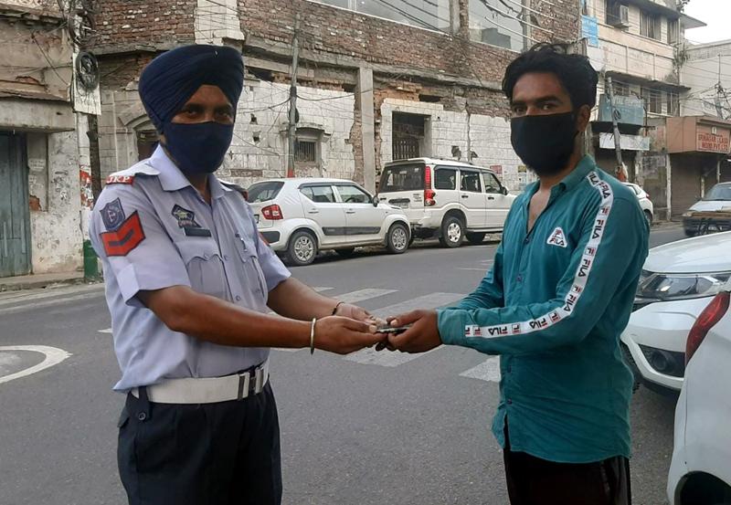 Le policier de la circulation Pawan Singh remet un mobile perdu à son propriétaire.