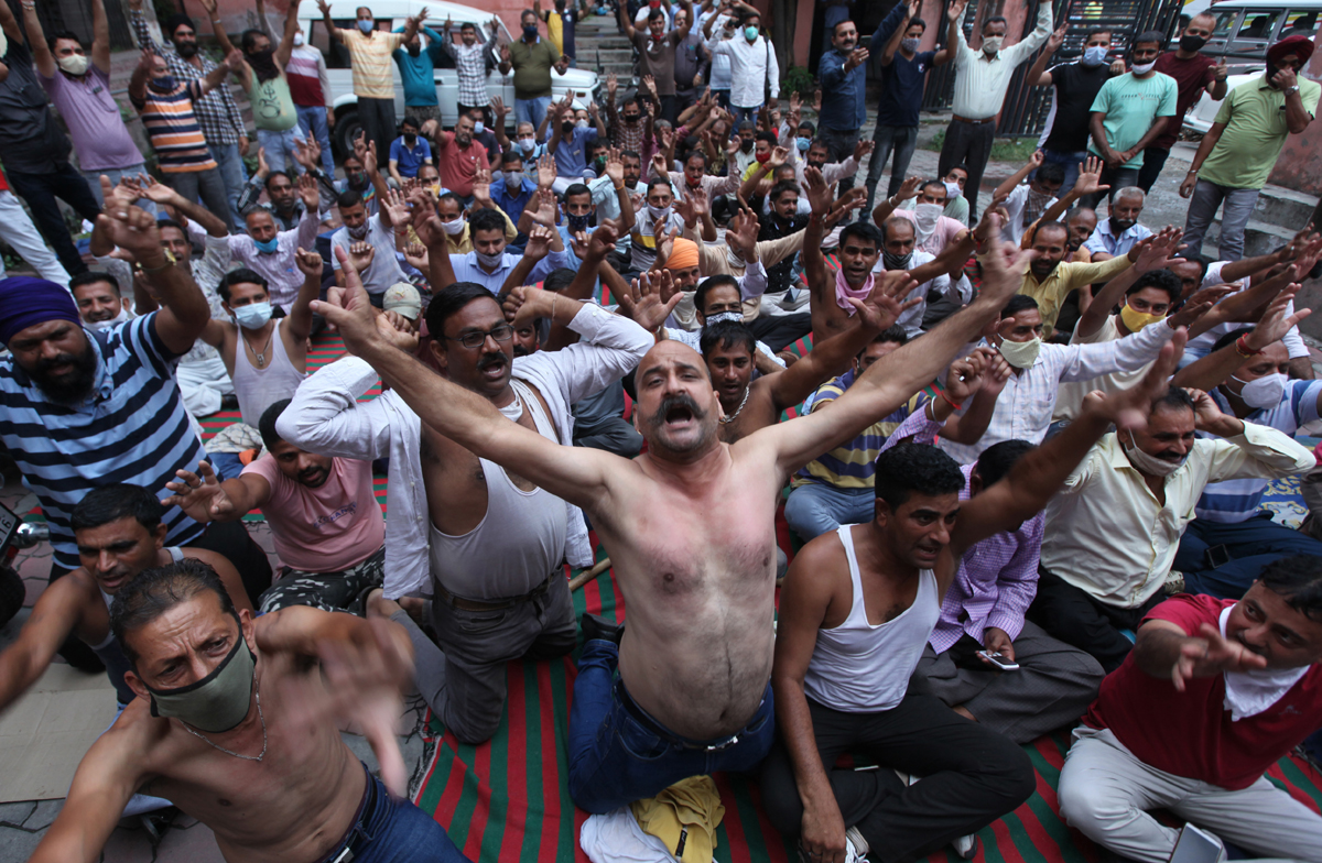 Pulling out their shirts, PHE daily wagers staging protest at Chief Engineer's office in Jammu on Tuesday. -Excelsior/ Rakesh
