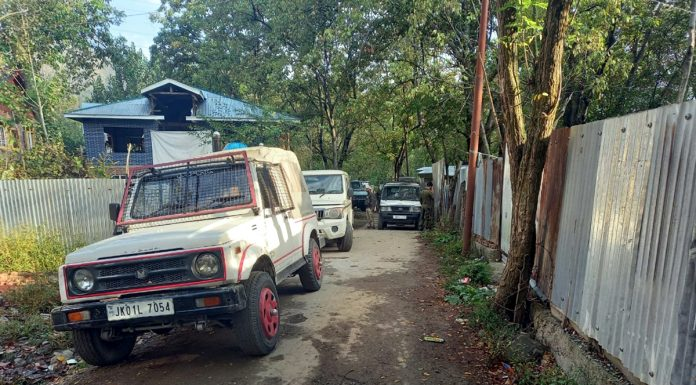 Police vehicles outside a house searched by the NIA at Sheeri Baramulla on Tuesday. -Excelsior/Abid Nabi
