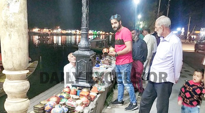 Tourists purchasing famous Kashmiri Paper Mache items from a vendor at Boulevard road on the banks of Dal lake in Srinagar. (UNI)
