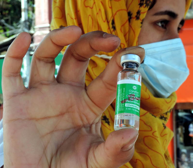 A paramedical staffer holding a COVID-19 vaccine in Lal Chowk area of Srinagar during a drive to immunize all citizens above 18 years to control the spread of Coronavirus infection on Tuesday. (UNI)
