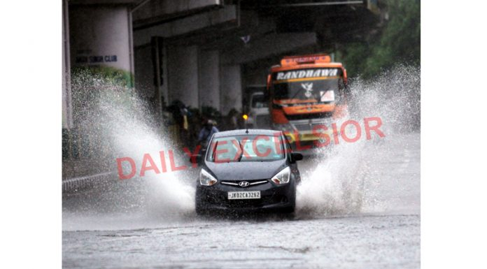Vehicles moving through water-logged road in Jammu on Wednesday. — Excelsior/Rakesh