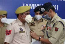 ADGP Mukesh Singh honouring a cop with DGP's Commendation Medal at Jammu on Monday.