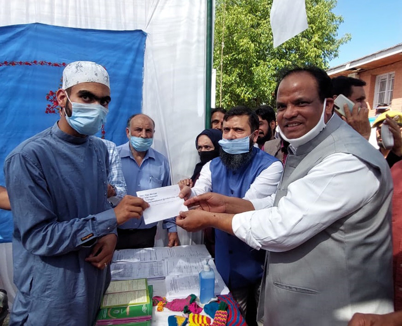 Union Minister felicitating an employee during visit to stalls of ICDS and Handicrafts Deptt at Kupwara.
