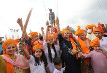 Rajput women and children celebrating birthday of Maharaja Hari Singh in front of his statue installed near main Tawi Bridge, Jammu. Excelsior/Rakesh