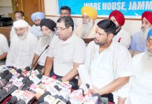 Vijay Singh Chib, senior member of All J&K Transport Welfare Association, flanked by other transporters addressing a press conference in Jammu on Friday. -Excelsior/Rakesh