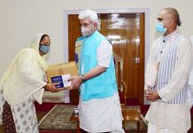 Lt Governor Manoj Sinha handing over grocery kit to a needy woman in Jammu on Wednesday.