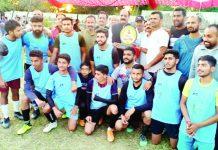 Former Minister SS Slathia presenting trophy to winning team at Vijaypur on Monday.