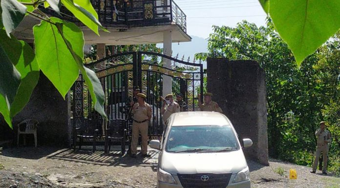 Cops guard a house during searches by the NIA in Poonch on Sunday.