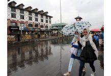 Girls walking down the Lal Chowk in Srinagar amid rainfall on Sunday. (UNI)