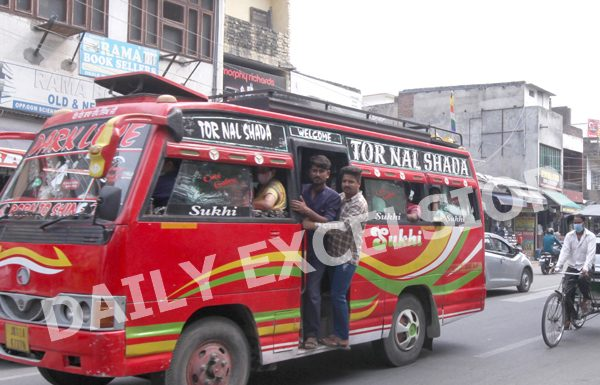 Without mask and hanging out from matador at Canal Road Jammu shows no check on violations by Traffic Police. —Excelsior/Rakesh