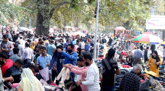 People buying warm clothes at weekly flea market in Srinagar on Sunday. -Excelsior/Shakeel