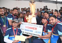 Winners celebrating victory by holding trophies with dignitaries at Kargil. —Excelsior/Basharat Ladakhi
