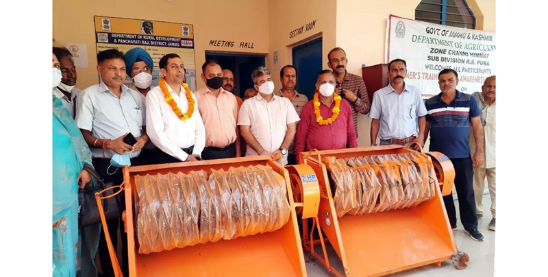 Director Agriculture K K Sharma and other officers posing with paddy threshers at Khojipur in Jammu.