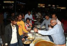 Ware House traders serving free langar to migrant labourers at Jammu Railway Station on Tuesday evening.